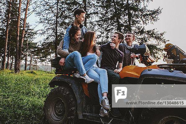 Friends sitting on quadbike at grassy field