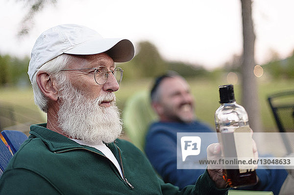 Man holding bottle while sitting with friend in yard