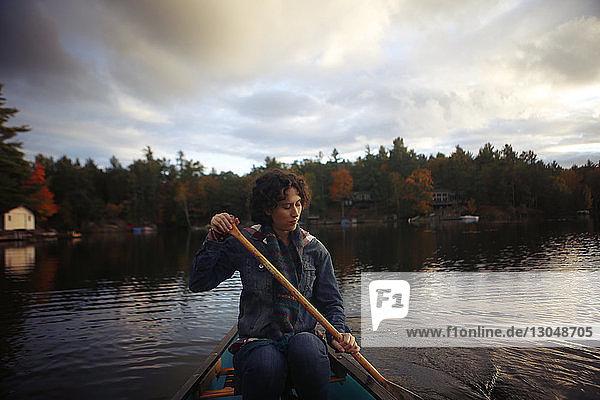 Frau paddelt auf dem See vor bewölktem Himmel bei Sonnenuntergang