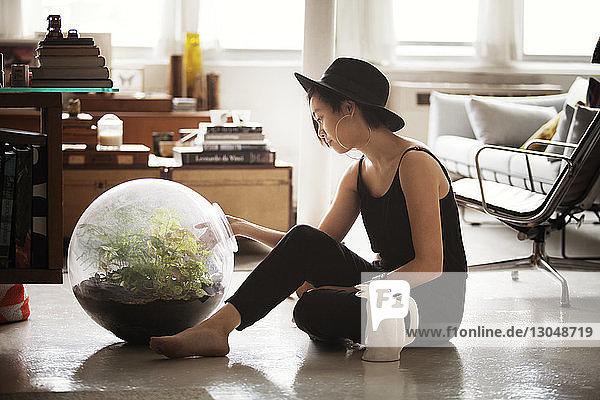 Seitenansicht einer Frau  die zu Hause Pflanzen in einem Glastopf untersucht
