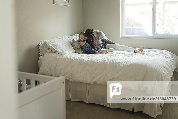 Mutter küsst Sohn,  während sie zu Hause auf dem Bett sitzt