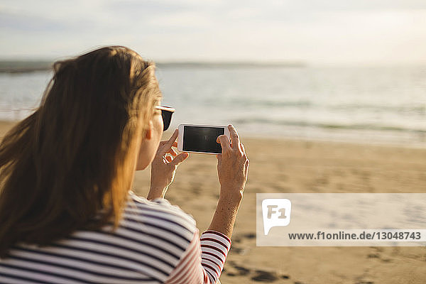 Rückansicht einer Frau  die das Meer fotografiert  während sie am Strand sitzt