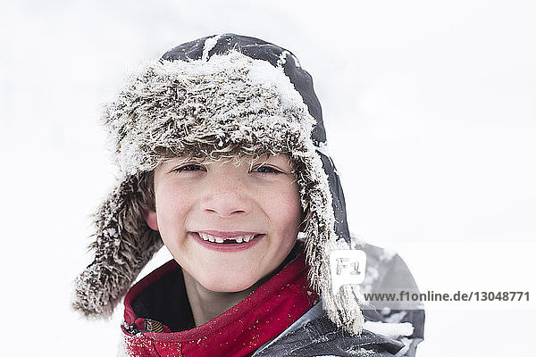 Close-up portrait of smiling boy standing on snow covered field