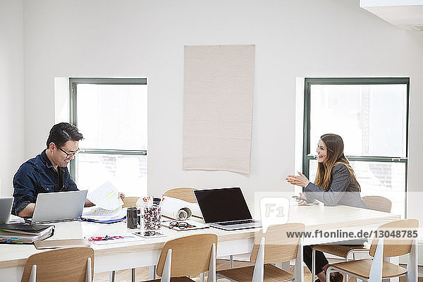 Happy businesswoman discussing with male colleague in creative office