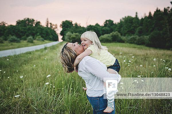 Glückliche Frau trägt Tochter bei Sonnenuntergang auf Grasfeld