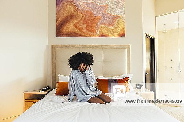 Lächelnde Geschäftsfrau sitzt im Hotelzimmer auf dem Bett