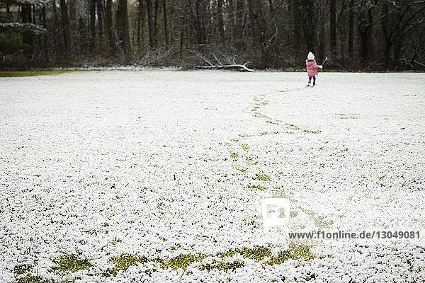 Rear view of girl walking on snowy field