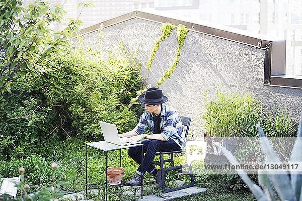 Mann benutzt Laptop  während er auf der Terrasse sitzt