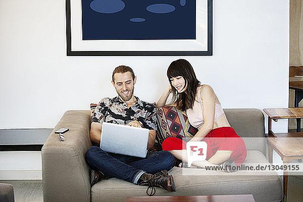 Geschäftsmann und Kollege schauen Laptop auf dem Sofa an