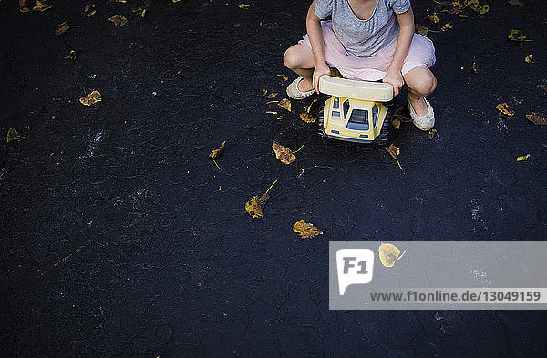 Low section of playful girl driving toy car on road