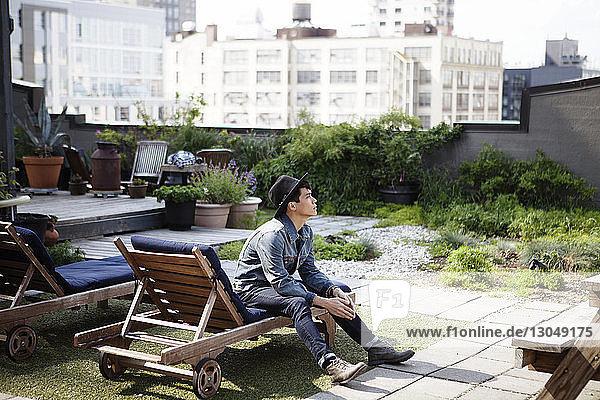 Nachdenklicher Mann sitzt auf einem Liegestuhl auf der Terrasse