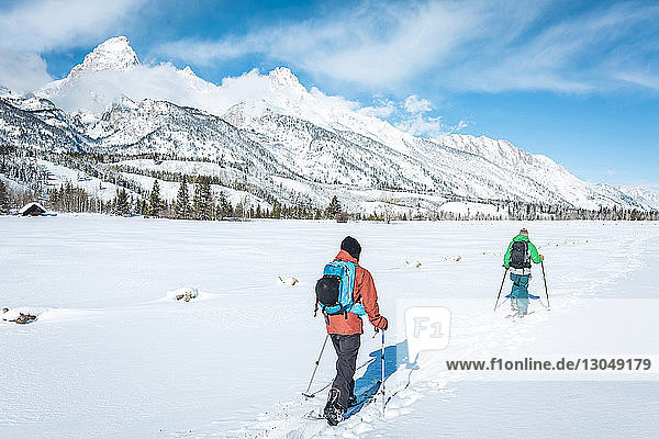 Rear view of skiers walking on field against snowcapped mountain