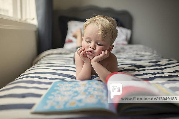 Junge mit Händen am Kinn liest Bilderbuch  während er zu Hause auf dem Bett liegt