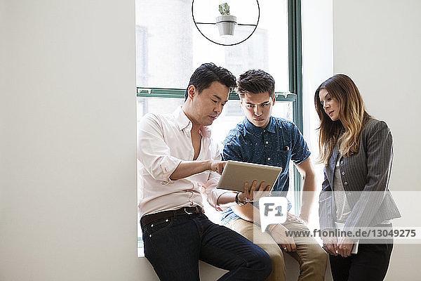 Geschäftsmann erklärt seinen Kollegen am Tablet-Computer im Büro die Strategie Geschäftsmann erklärt seinen Kollegen am Tablet-Computer im Büro die Strategie