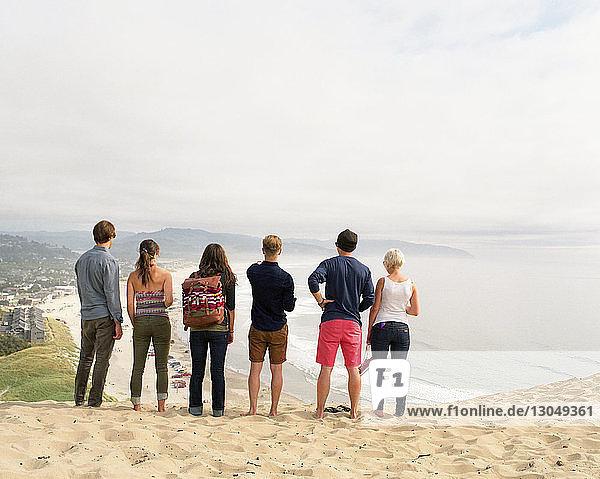 Rückansicht von Freunden  die auf Sand am Strand gegen den Himmel stehen