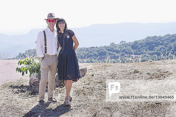 Portrait of newlywed couple standing on mountain against sky during sunny day