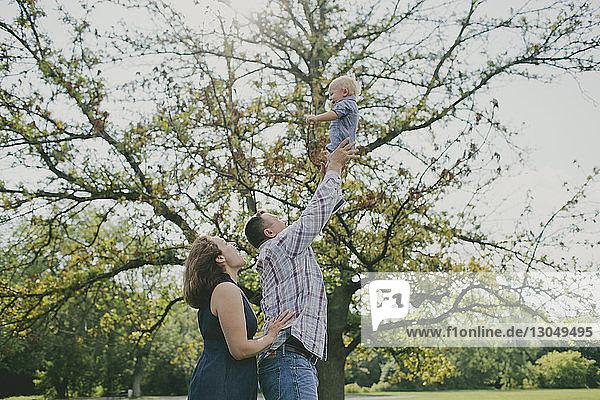 Glücklicher Vater wirft kleinen Jungen in die Luft