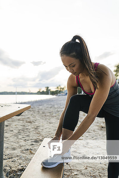 Woman tying shoelace at beach against sky