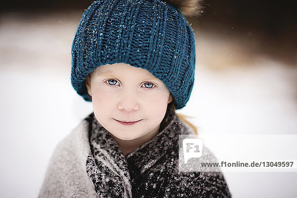 Portrait of smiling girl standing outdoors during winter