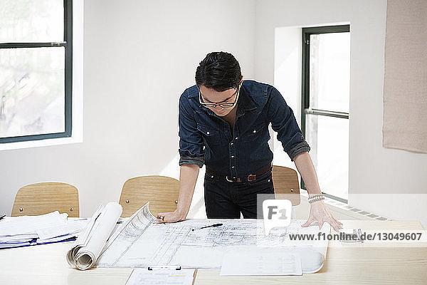 Geschäftsmann analysiert Blaupause am Schreibtisch im Kreativbüro Geschäftsmann analysiert Blaupause am Schreibtisch im Kreativbüro