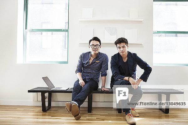 Porträt selbstbewusster Geschäftsleute auf der Bank sitzend in einem kreativen Büro Porträt selbstbewusster Geschäftsleute auf der Bank sitzend in einem kreativen Büro