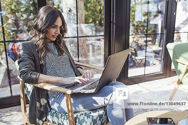 Businesswoman using laptop computer in coffee shop