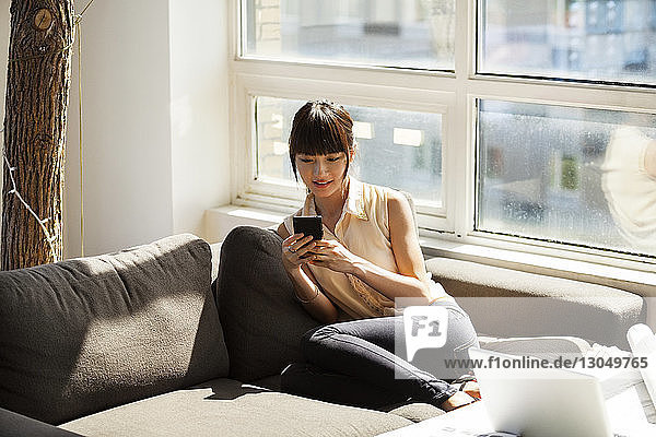 Businesswoman using smart phone while sitting on sofa in creative office