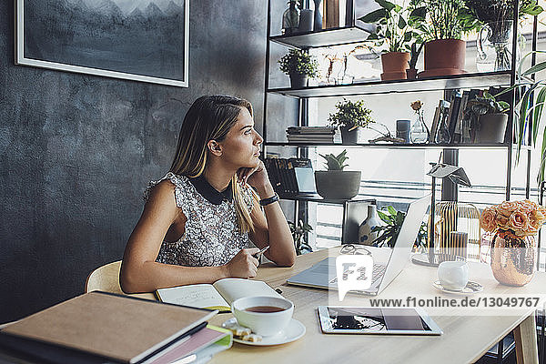 Thoughtful businesswoman sitting at table in home office