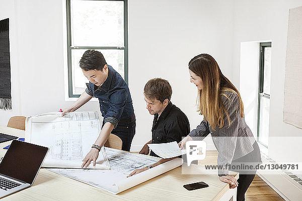 Geschäftsleute beim Analysieren von Entwürfen im Kreativbüro Geschäftsleute beim Analysieren von Entwürfen im Kreativbüro
