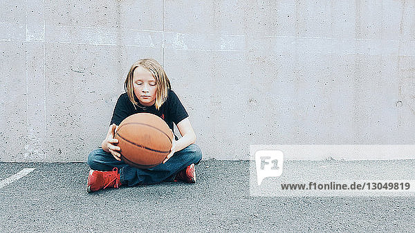 Boy holding basketball while sitting on footpath against wall