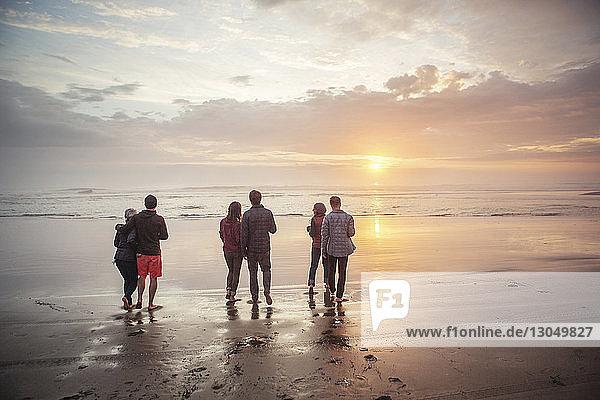 Rückansicht von Paaren  die bei Sonnenuntergang am Strand am Ufer spazieren gehen