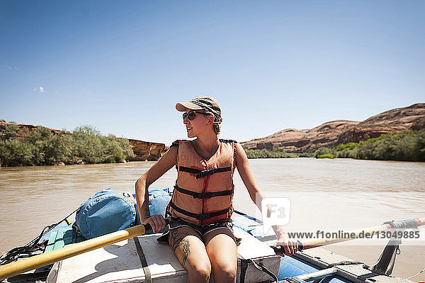 Woman wearing life jacket while sitting in inflatable raft on San Juan River against clear sky during summer