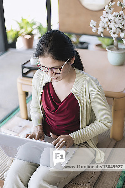 Woman using laptop computer while sitting at home