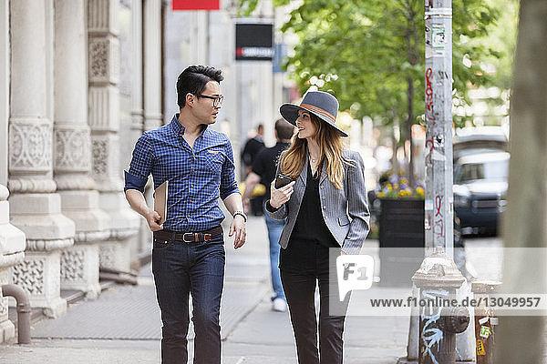 Geschäftsleute unterhalten sich beim Gehen auf dem Bürgersteig in der Stadt