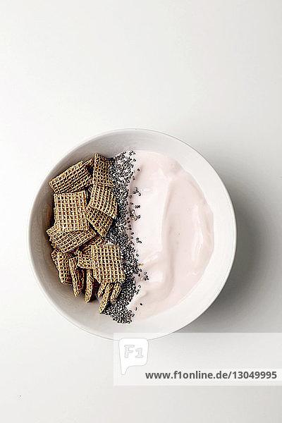 Draufsicht auf das Frühstück  das in einer Schüssel auf weißem Hintergrund serviert wird