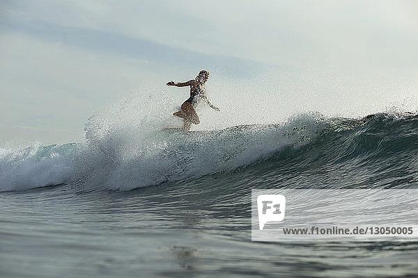 Frau surft im Meer gegen den Himmel
