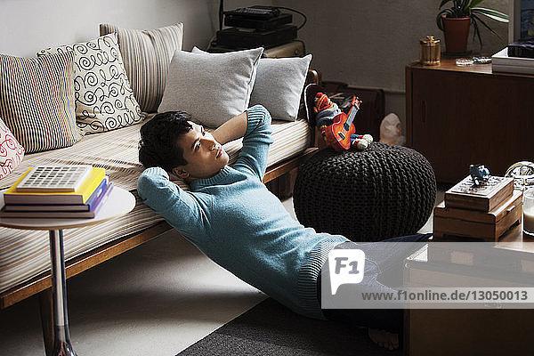 Trauriger Mann sitzt auf dem Boden im Wohnzimmer