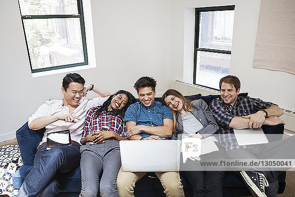 Cheerful business people using laptop while relaxing on sofa in office