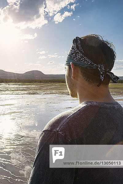 Rear view of man looking at view while standing against sky