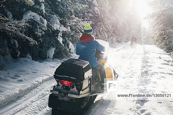 Rear view of woman riding snowmobile on snow covered field