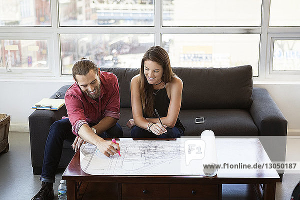 High angle view of business people looking at blueprint in creative office