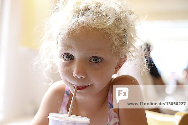 Portrait of cute girl having drink at restaurant