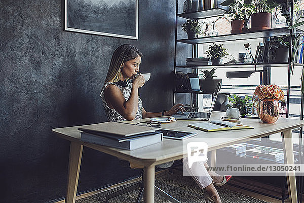 Businesswoman drinking coffee while working at laptop computer in home office