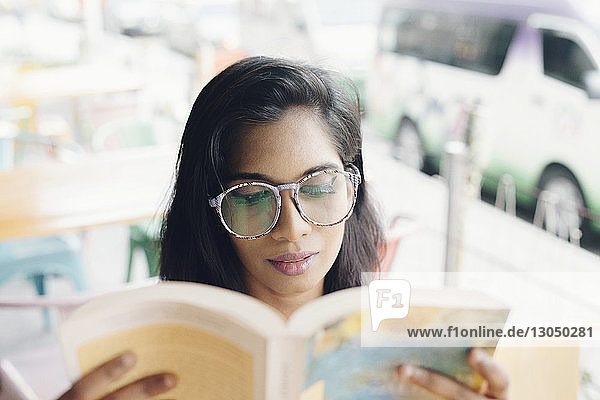 Young woman wearing eyeglasses while reading book at sidewalk cafe