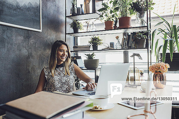 Smiling businesswoman working on laptop at home office
