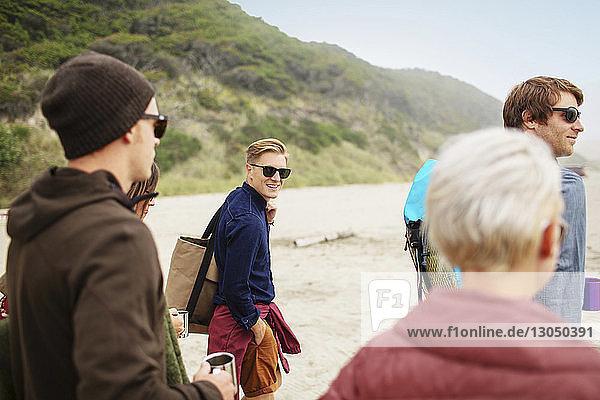 Porträt eines glücklichen Mannes mit Freunden am Strand