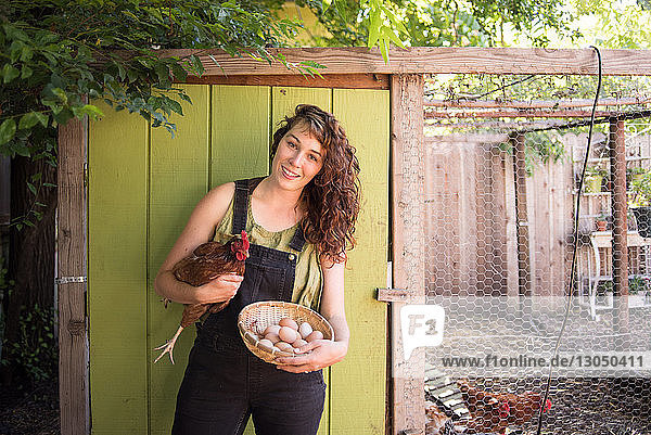 Portrait of happy woman holding hen and egg basket while standing against birdcage at farm