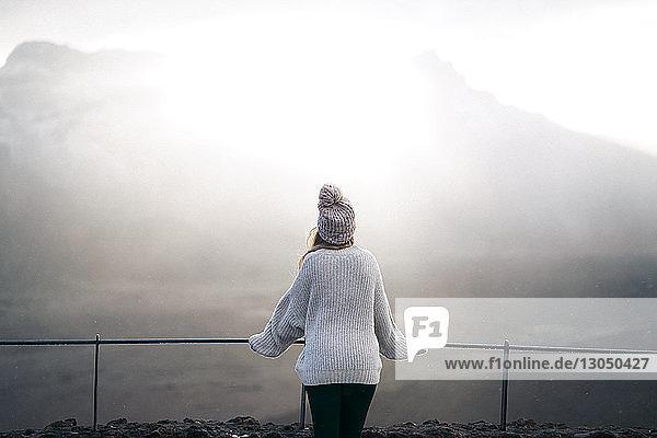 Rückansicht einer Frau  die am Beobachtungspunkt am Geländer gegen den Berg steht
