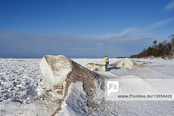 Rückansicht einer Wanderin auf verschneitem Feld vor blauem Himmel