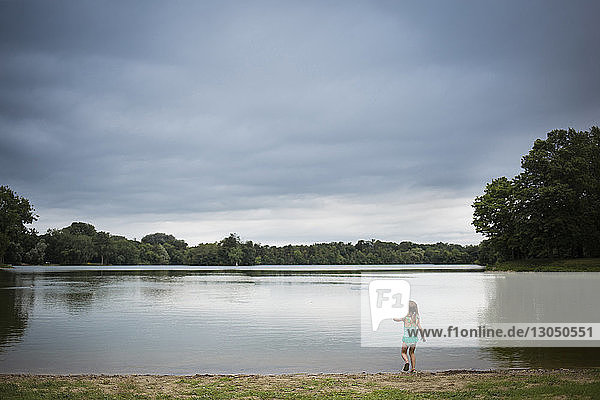 Rear view of girl standing at lakeshore against cloudy sky